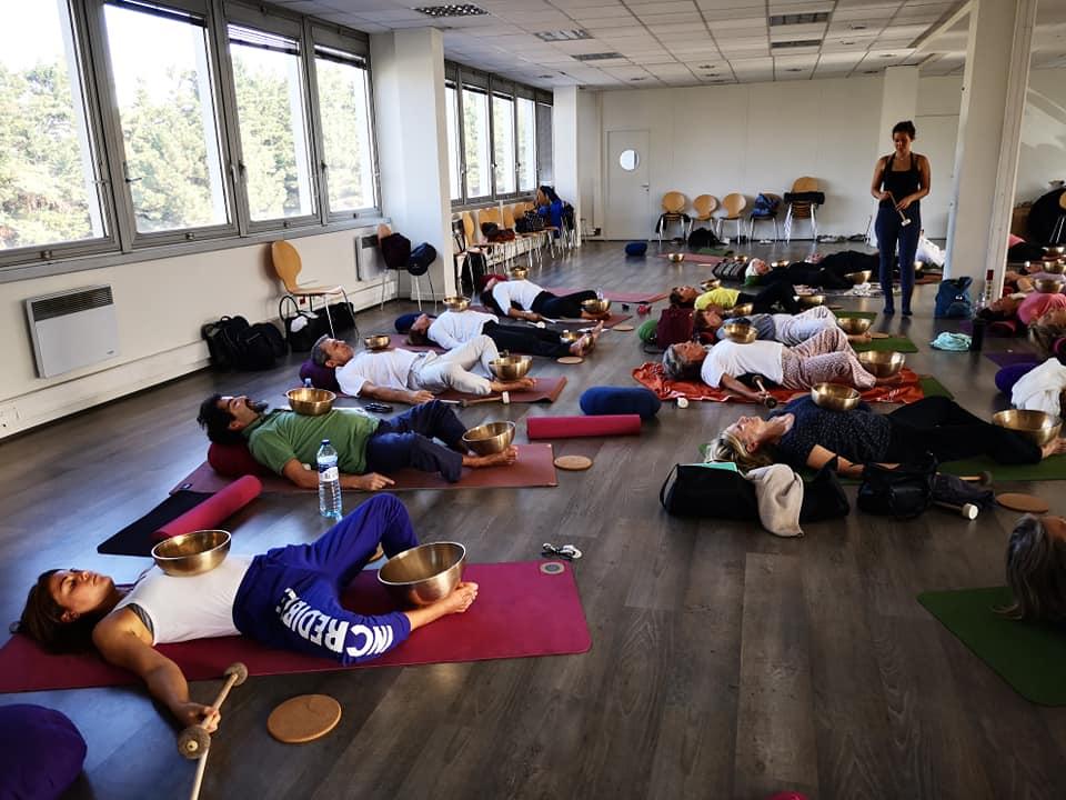 photo où l'on voit des yogis faire des postures de yoga avec les bols Peter Hess