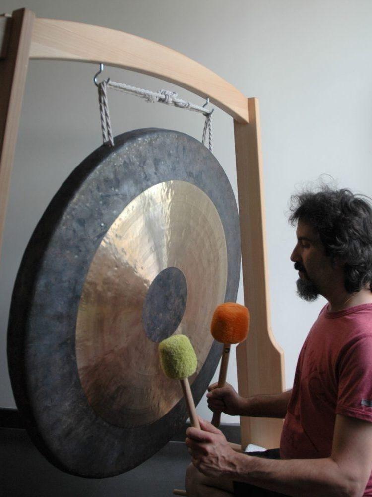 photo où Dominique joue du tam tam gong avec 2 mailloches
