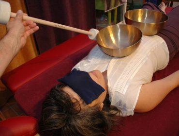 photo d'une personne recevant un massage sonore en position dorsale avec deux bols tibétains